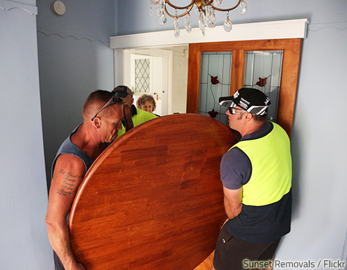 Moving a dining room table requires a lot of care and skill.